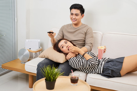 Young couple in love sitting on a brown sofa and watching television in the living room.
