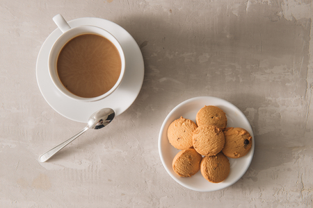 White cup of creamy coffee with butter cookies and stainless teaspoon isolated on white background, clipping path Stock fotó