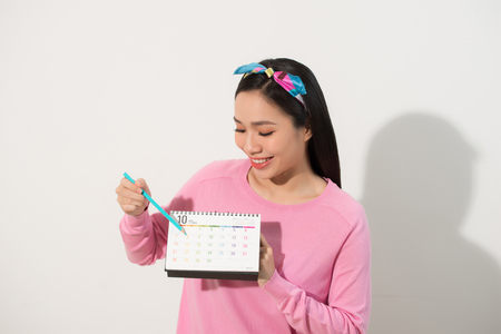 Portrait of a smiling young girl checking her periods according to calendar isolated over white background 版權商用圖片