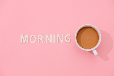 MORNING text with a cup of coffee with shadow on pink background.