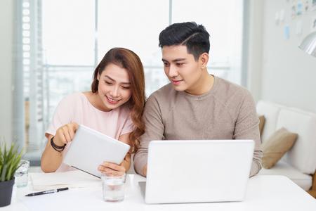Schöne junge Geschäftsfrau und schöner Geschäftsmann in formellen Anzügen verwenden Geräte, sprechen und lächeln, während sie im Büro arbeiten