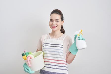 Porträt der glücklichen Frau, die in ihren Händen Reinigungsprodukte hält, während sie zu Hause steht und anfängt zu reinigen.
