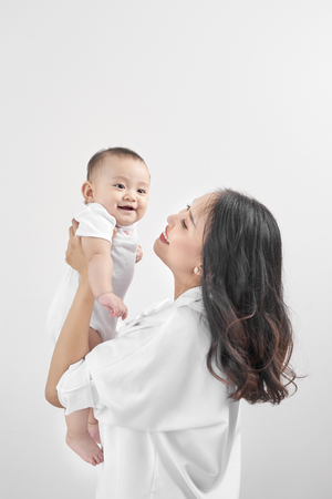 Happy loving family. Young smiling mother hugging laughing baby. Stock Photo - 106876182