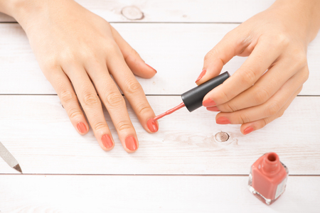 Female hands doing nail polish in coral color