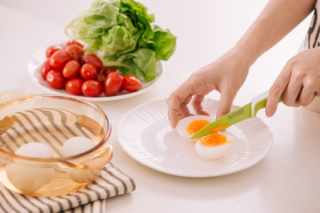 Close up of females hands cutting boiled egg for his breakfast and mixed vegetables on white wooden background