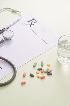 Stethoscope, pills and glass of water on light green background. medicine concept