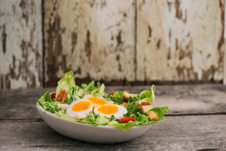 Elevato angolo di visione di una nutriente insalata di verdure con uova sode a fette, servito su una piastra bianca sulla parte superiore di un tavolo di legno