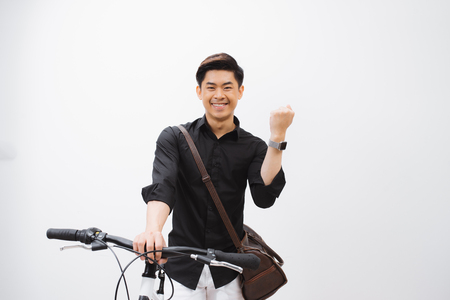 Young handsome asian man against the backdrop of white wall sits on a bicycle 版權商用圖片