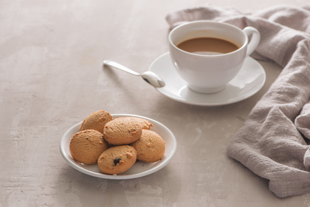 White cup of creamy coffee with butter cookies and stainless teaspoon isolated on white background, clipping path Stock Photo