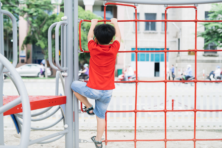 little boy playing on monkey bars at playground