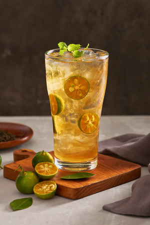Glass of fresh drink cumquat lemonade tea.
