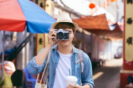 Young asian man traveler shopping walking on street market