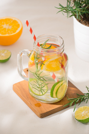 Infused water with lime, orange, apple and rosemary. Cold refreshing detox summer drink .Selective focus Stok Fotoğraf