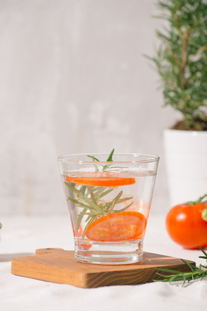 Delicious refreshing water with rosemary and tomato in glass on table