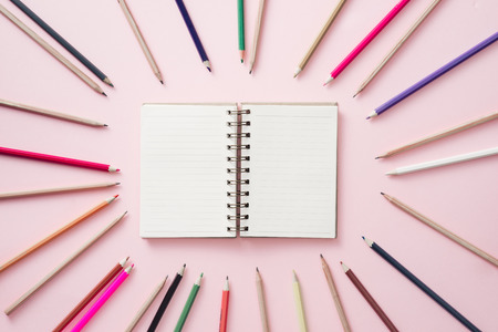 Notebooks in center with Bright colored pencils lined around the perimeter of the pink background.