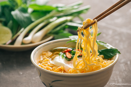 closed up instant noodles with vegetables on chopstick isolated on dảk stone background, junk food or fast food concept. Banco de Imagens