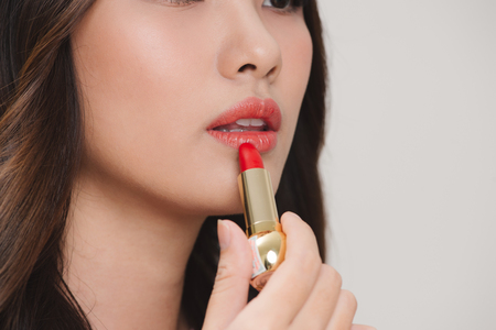 Young happy smiling woman applying lipstick, isolated over white background 写真素材