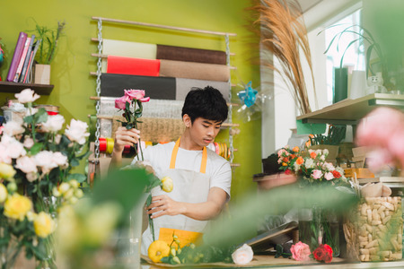 Small business. Male florist making rose bouquet at counter desk in flower shop. Man assistant or owner in floral design studio, making decorations and arrangements. Flowers delivery, creating order