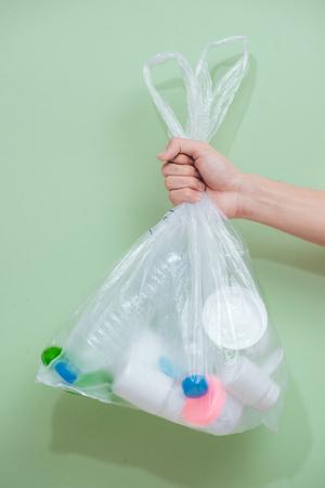 Female hand holding a waste bag isolated on white background. Reklamní fotografie