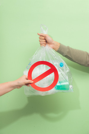 Male hand holding a waste bag isolated on green background.