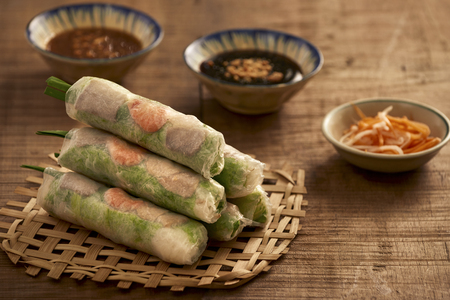 Vietnamese spring rolls - rice paper, lettuce, salad, vermicelli, noodles, shrimps, fish sauce, sweet chili, soy, lemon, veletables. Copy space. Asian and Vietnam food. Traditional national cuisine Stock Photo
