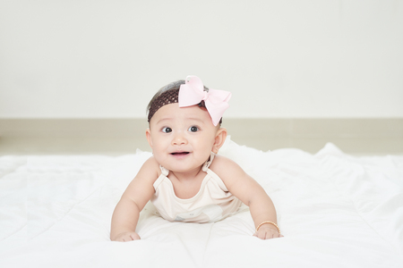 Baby girl smiling on the floor isolated on white 스톡 콘텐츠
