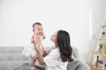 Mother and baby laugh together at home. They are sitting on the sofe in a brightly lit living room at the weekend together, lazy morning, warm and cozy scene. Selective focus 写真素材