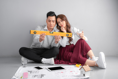 Young couple examining blueprints of they new home. Real estate and Moving house concept. 写真素材