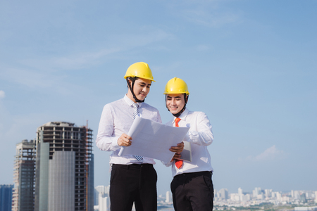 View of a Engineer and worker watching blueprint on construction site Standard-Bild