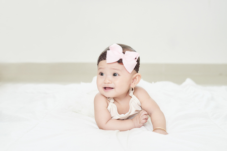 A baby girl is crawling along the floor with an inquisitive look on her face. Horizontal shot.