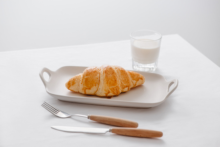 Freshly baked croissants on dish with glass of soy milk on white table for breakfast