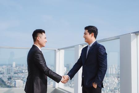 twee knappe zakenlieden die elkaar begroeten op straat