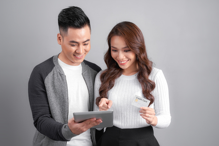 Happy Asian couple using tablet and credit card for online shopping