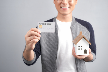 Man holding little wooden house in one hand and credit card in other. Looking at camera and smiling.