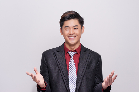 Handsome and well dressed businessman in a suit, tie and vest, standing against a white background smiling towards camera.