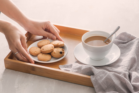 Hand putting cookies on plate into tray. Breakfast concept with coffee Stock Photo