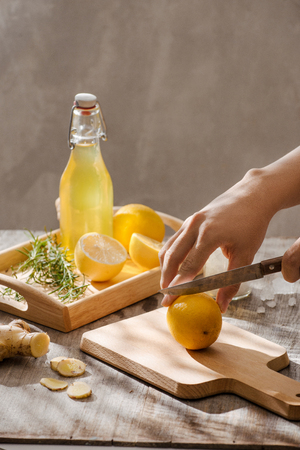 Refreshing summer drink with lemon, ginger, rosemary and ice on rustic wooden table, copy space Stockfoto - 114564472