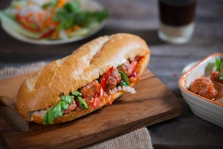 Vietnamese sandwich bread with meatballs in tomato sauce and radish, carrot pickle, cucumber, coriander. Standard-Bild
