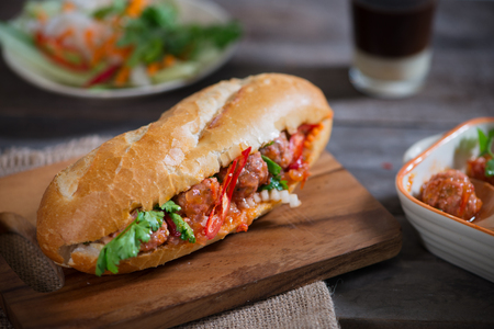 Vietnamese sandwich bread with meatballs in tomato sauce and radish, carrot pickle, cucumber, coriander. Stockfoto