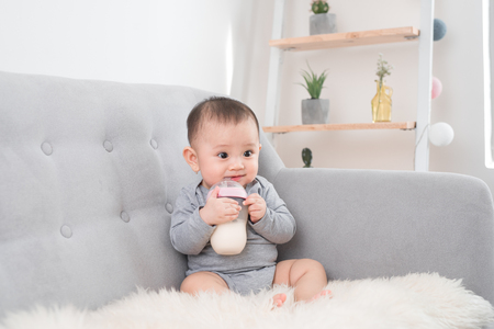 Kleine schattige babymeisje, zittend in de kamer op de bank consumptiemelk uit de fles en glimlachen. Blije baby. Familie mensen indoor interieurconcepten. Jeugd beste tijd!