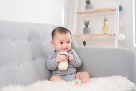 Kleines niedliches Baby, das im Zimmer auf Sofa sitzt, trinkt Milch von Flasche und lächelt. Glückliches Kind. Innenraumkonzepte für Familien. Beste Zeit für die Kindheit!