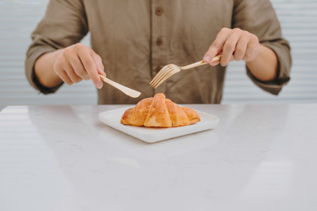 A man eating fresh croissant baked on Saturday morning Stock fotó - 109261169