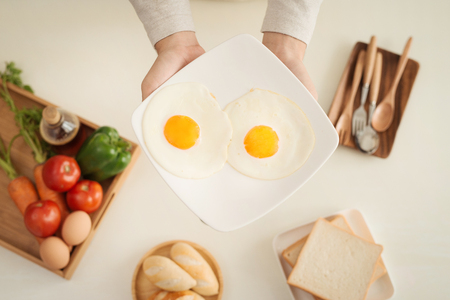 Hands of man prepare breakfast with eggs and bread.