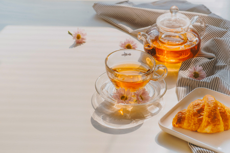 cup of tea on a tray and twigs with flowers on a table near a window of a summer sunny morning