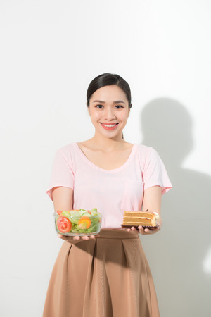 Half-length portrait of very beautiful woman holding small cake, fresh vegetables.
