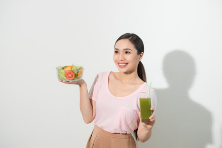 Woman with green detox smoothies, salad in glass bowl isolated on white background.