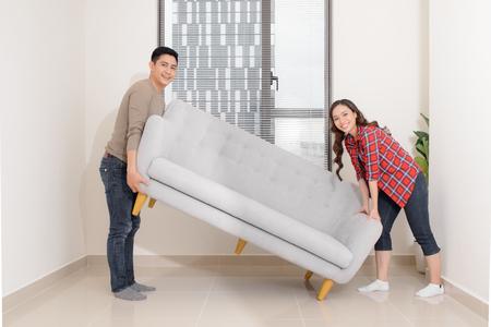 Pareja sonriente llevando una silla moderna juntos colocando muebles que se mudan a una nueva casa, una familia joven discutiendo el diseño de interiores de mejora de la casa mientras amuebla la sala de estar, remodelación y renovación Foto de archivo