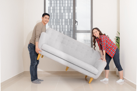 Smiling couple carrying modern chair together placing furniture moving into new home, young family discussing house improvement interior design while furnishing living room, remodeling and renovation 免版税图像