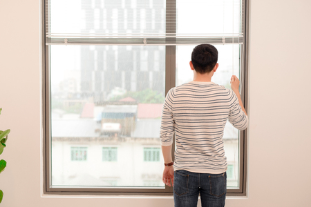 Young man standing near window in hotel room 版權商用圖片 - 109355402