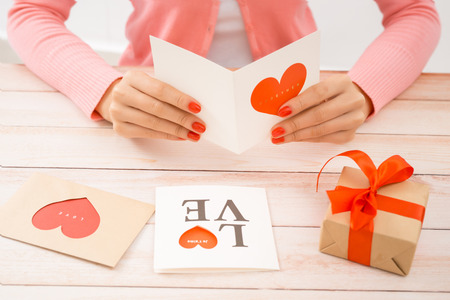 Female hands holding Valentines day love letter on wooden background.
